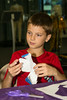 """Making a Star Craft""<br /> <br /> Grandson J, almost 9, is very ""into"" science. So James and I took him to the Space Foundation Discovery Center in Colorado Springs. Here J watches as a very nice woman employee showed him how to make an icosahedron model of the constellations. It took a lot of coordination!"