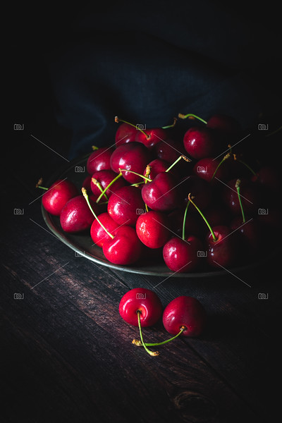 Dark red cherries on a pewter plate