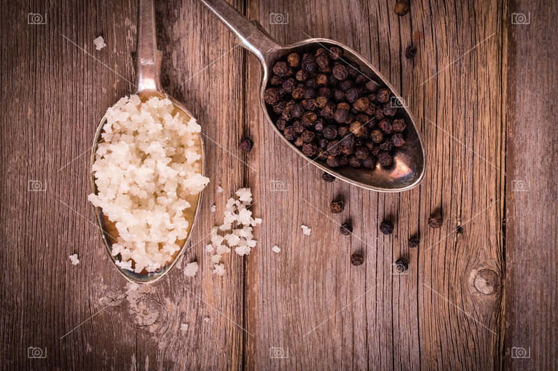 Vintage effect image of tarnished silver spoons filled with salt crystals and black peppercorns, over rough wood background. Space for your text