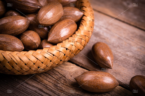 Whole pecan nuts in a wicker bowl, over vintage wood background.