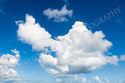 Blue Sky with White Fluffy Cumulus Clouds Background