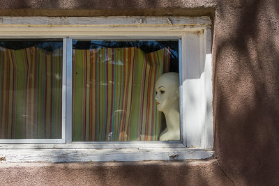 A mannequin peers out of a window. Taken in Mesilla, New Mexico, USA.