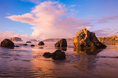 """Evening at Bandon Beach""  I wanted to take advantage of the big cloud and light on this particular evening. So I used a Cokin blue/yellow polarizer. I did have to remove some vignetting from the corners, easy to do with Photoshop's content-aware fill. Taken at Bandon Beach, Oregon, USA."
