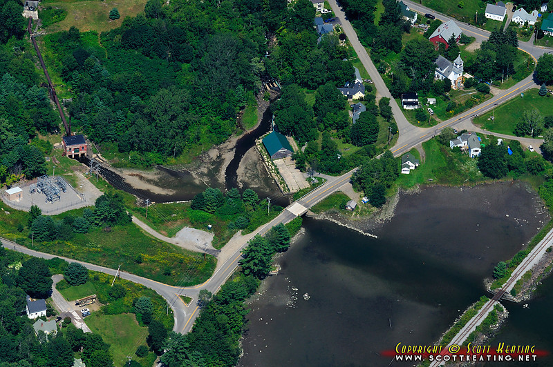 """The stream leading down through the center of the frame is actually part of a man made """"fish ladder"""". In the 1700s a mill blocked the natural path for the Alewife fish to move between Damariscotta Lake and the Damariscotta River. To correct the problem the fish ladder was built. The building in the center of the frame appears to be the remnants of an old fishery, and the small red building on the left is a hydro-electric generating station."""