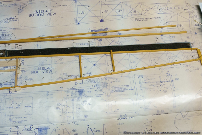 The top fuselage stringer is pinned against a straight-edge to ensure the top of the fuselage is flat. The bottom stringer is pinned to the plan outline. With the tailpost glued in place the vertical parts can be cut.