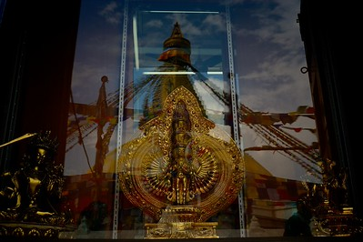 a window with religious art craft (left to right: Manjushree, Thousand Arms Avalokitesvara, Tara) reflects the great stupa of Boudhnath