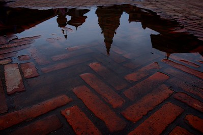 a puddle in Durbar square reflects its temples