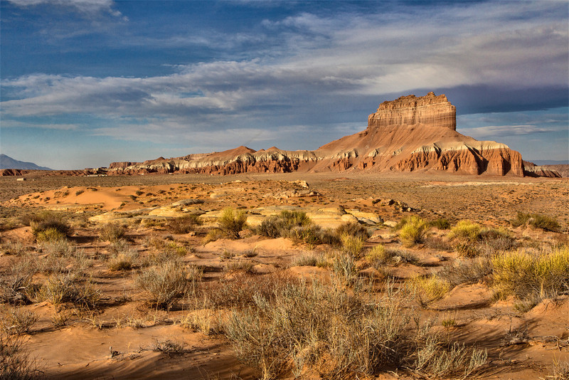 This is a view of Wild Horse Butte, one  of the large monoliths you see as you approach Goblin Valley State Park in Utah. Relatively few people visit Goblin Valley State Park, which is a pity since the eroded sandstone formations are every bit as beautiful as the more famous Utah national parks further south, although on a much smaller scale. The park lies at the edge of the vast San Rafael Desert, 12 miles from the small village of Hanksville.