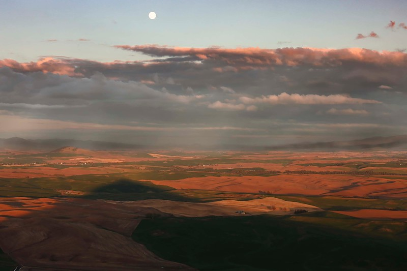 Full moon rising, over shadow of Steptoe Butte from setting sun