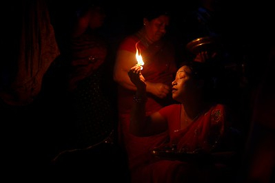 On the third day of Bisket Jatra, Shiakotyako is a day dedicated to offerings and blessings at Bhairab's chariot. Since early morning devotees come from every part of Bhaktapur to do their offers. Here a woman offers fire.