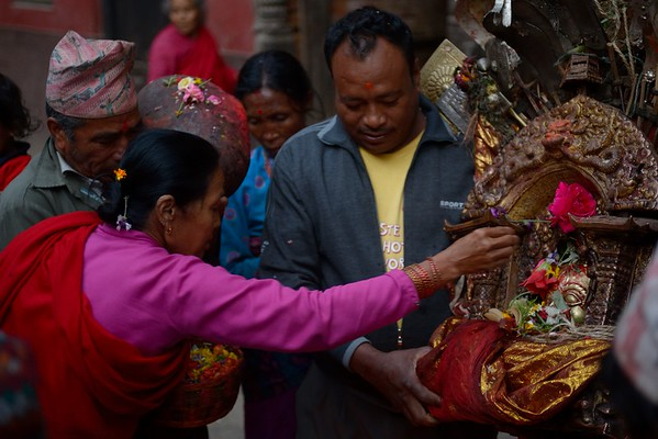 A woman worshiping Bhairab with flowers