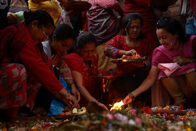 A group of women making offers, lighting lamps and burning incense