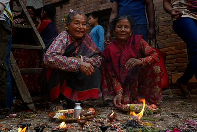 Elder women smile after they completed their ritual at the chariot. On their plate is rice, incense eggs, colored powder, roksi (a local liquor) and the head of a chicken.