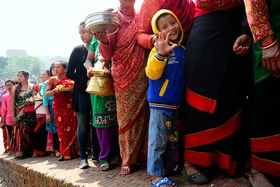 a child greets from a queue of devotees