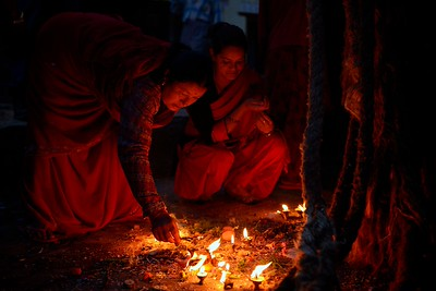 women lighting lamps near Bhairab chariot's ropes