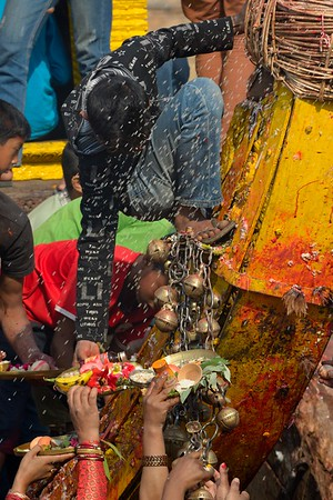 under a rain of rice, a boy on Beta Sin receives plates of offers from devotees, give the offers to beta Dyo and gives back blessings