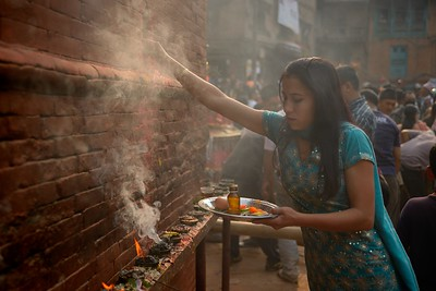 Sindur Jatra: a young woman worshiping at a temple into a cloud of incenses