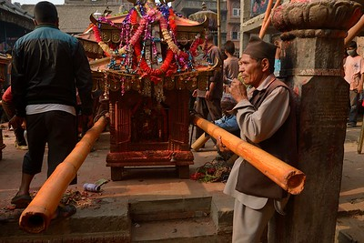 Sindur Jatra: a man smoking nearby the palanquin he's going to carry during the festival