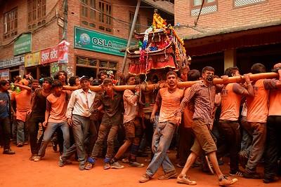 During Sindur Jatra devotees throw orange powder and roam Thimi village carring palanquins with local gods