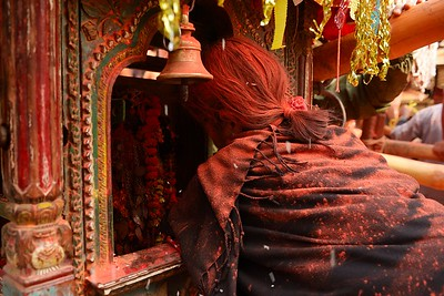Sindur Jatra: a woman covered with well-wishing orange powder worships a god inside a palanquin