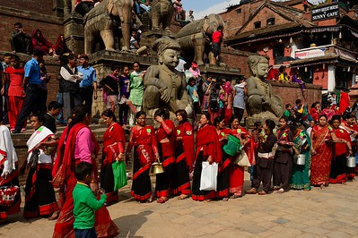 women in the traditional black and red Bhaktapur sari form a long line waiting for their turn in bringing offers at temples