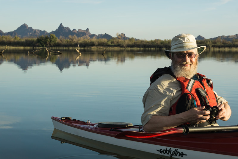 Andy Baird kayaks on the backwaters of the Colorado River, with The Needles rock formations in the background. Taken at Havasu National Wildlife Refuge, Arizona, USA.