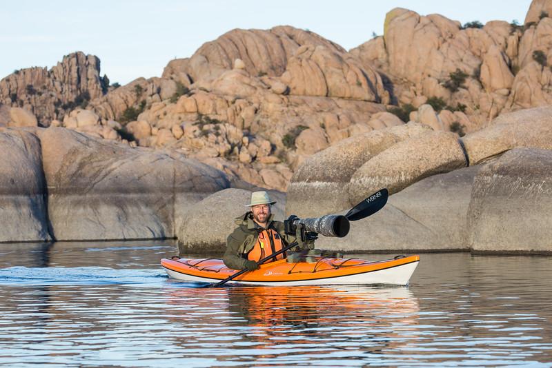 Nature photographer James Hager paddles his kayak while preparing to take photos. Taken from the kayak on Watson Lake, Prescott, Arizona, USA.
