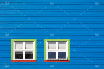 Green and red windows on blue wall