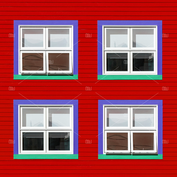 Purple and green windows on red wall