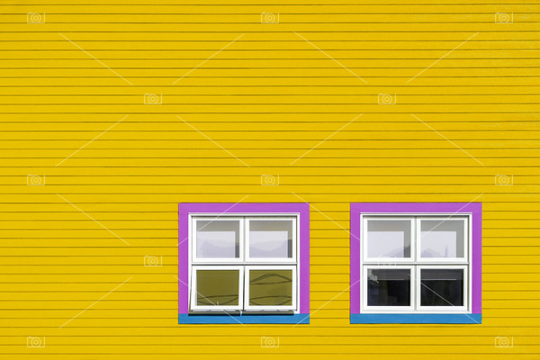 Pink and blue windows on yellow wall
