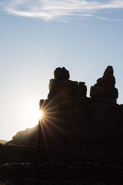A sunburst peeks out from behind Battleship Rock. Taken in Valley of the Gods, Bears Ears National Monument, Utah, USA.