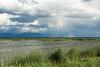 A rainbow forms among storm clouds. Taken at Bear River Migratory Bird Refuge, Utah, USA.