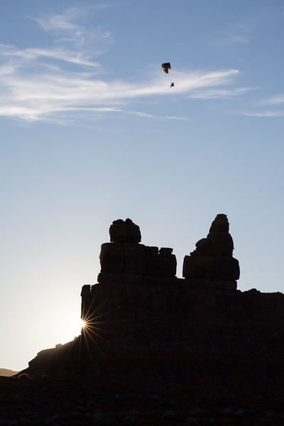 A powered paraglider pilot flies above Battleship Rock as the setting sun peeks from behind the rock formation. Taken in Valley of the Gods, Bears Ears National Monument, Utah, USA.