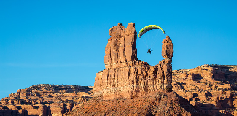 A powered paraglider pilot flies around the rock formations known as Lady in the Bathtub and Balanced Rock. Taken in Valley of the Gods, Bears Ears National Monument, Utah, USA.