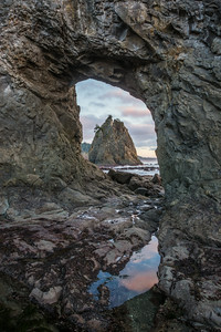 """Looking Through""  Sunset view of a sea stack through a hole in another sea stack. Taken at Rialto Beach, Olympic National Park, Washington, USA."