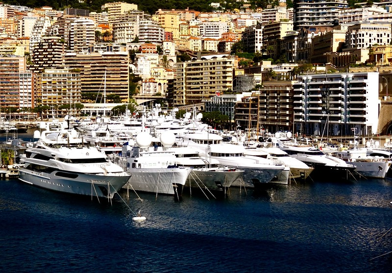 Yachts lined up in the harbor of Monaco, the tiny city / state on the Mediterranean Sea surrounded by France and next to the Italian Riviera.