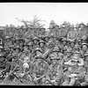 Group portrait of part of a New Zealand battalion that fought successfully at the Battle of Messines, Belgium. Some of the troops are wearing souvenired German helmets and caps. Photograph taken probably France in June 1917 by Henry Armytage Sanders