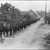 New Zealand troops marching though a residential area in France between Gommecourt and Sailly au Bois. Photograph taken circa 8 September 1918 by Henry Armytage Sanders