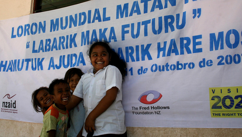 Local children with a Fred Hollows banner. Credit: A Palagyi, Fred Hollows Foundation