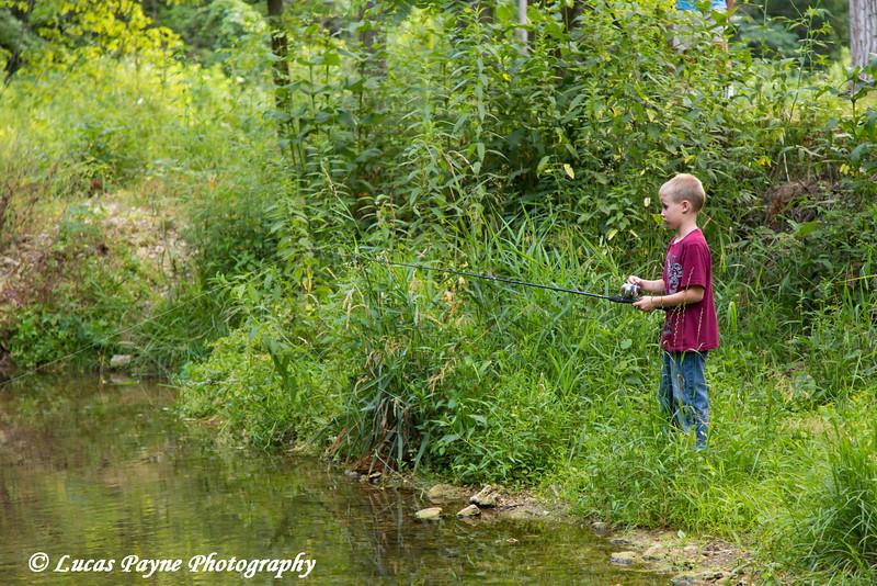 Boy fishing in Bear Creek at Bixby State Preserve near Edgewood in Northeast Iowa<br /> <br /> July 11, 2012
