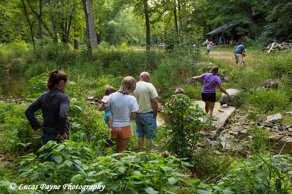 Family crossing Bear Creek on hiking trail leading to the Ice Cave at Bixby State Preserve near Edgewood in Northeast Iowa<br /> <br /> July 11, 2012