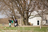 Amish girls raking yard near Hazelton, Iowa.<br /> April 08, 2010