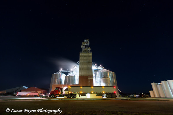 Grain truck parked in front of the Edgewood Feed Mill grain elevator site at night, Edgewood, Northeast Iowa.<br /> <br /> October 21, 2013