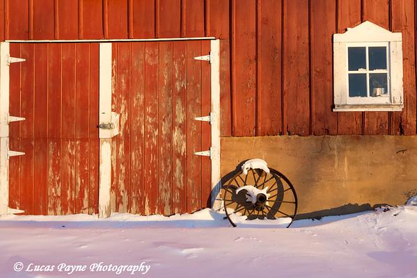 Old wagon wheel leaning against a red barn with freshly fallen snow on a farm near Edgewood in Northeast Iowa<br /> <br /> December 21, 2012