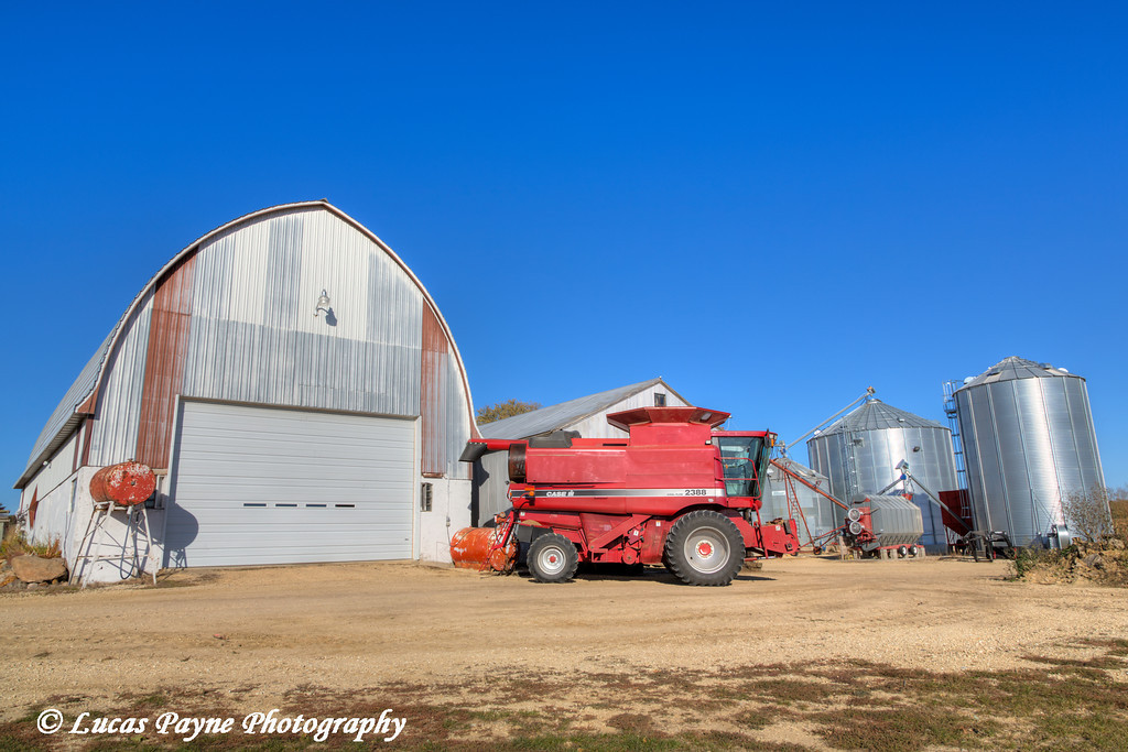 Red combine in front of a barn and grain bins on a farm in Northeast Iowa. <br /> <br /> October 27, 2013