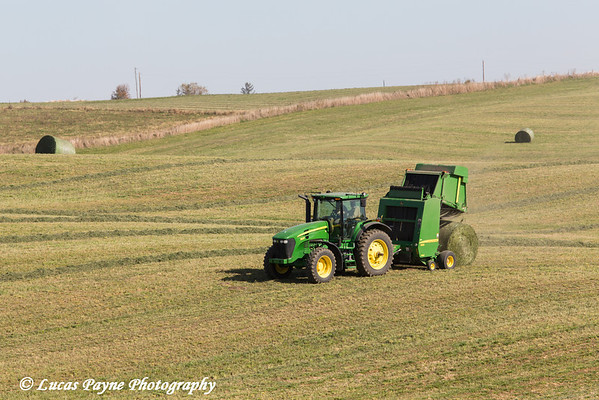 Tractor and baler unloading a completed round bale of hay on a farm in Northeast Iowa.<br /> <br /> October 27, 2013