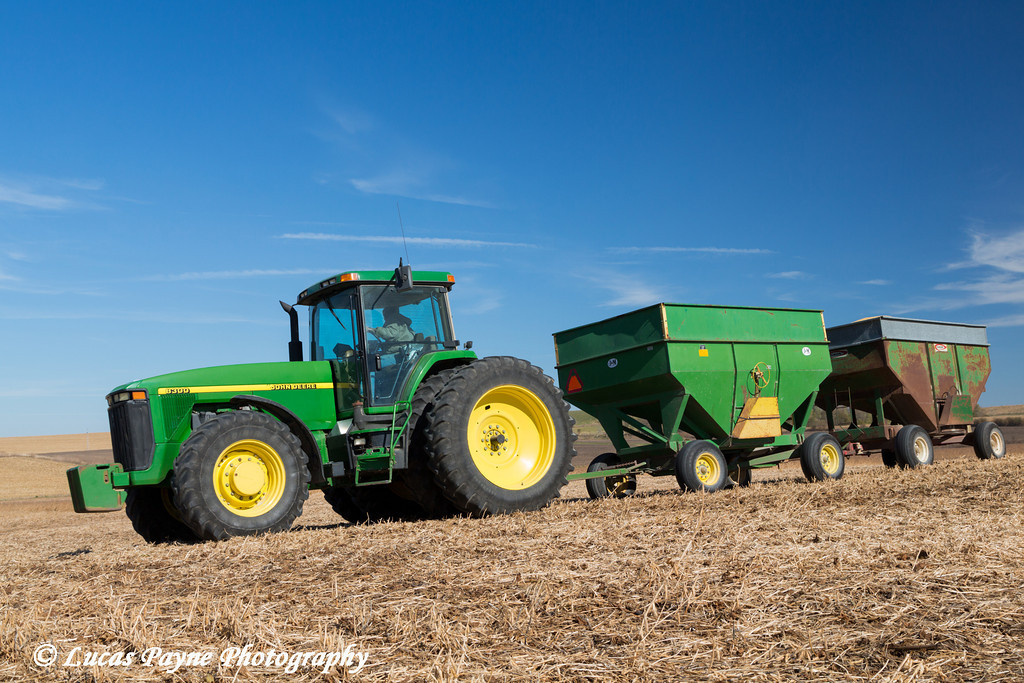 Farmer driving a tractor hauling two grain wagons full of soybeans in Northeast Iowa.<br /> <br /> October 27, 2013