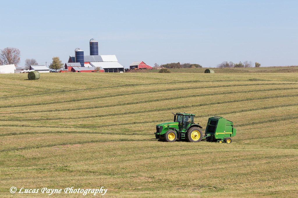 Tractor and baler collecting hay to make round bales on a farm in Northeast Iowa.<br /> <br /> October 27, 2013