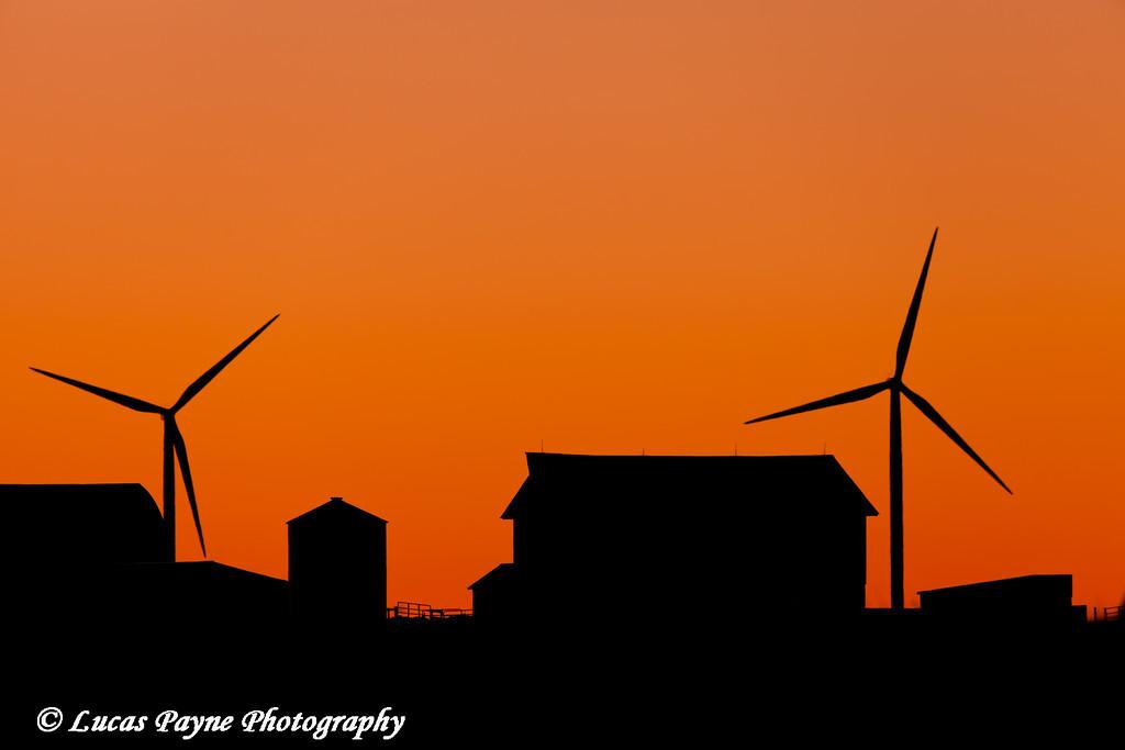 Elk Wind Energy Farm and barn silhouetted at sunrise near Edgewood in Eastern Iowa<br /> December 25, 2011