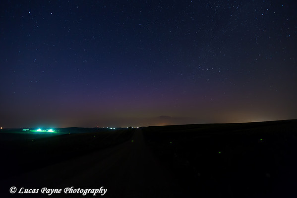 Faint glow of the Aurora Borealis (Northern Lights) low on the horizon with a firefly flying across the foreground from Highway 3 near Colesburg, Iowa<br /> <br /> July 14, 2012